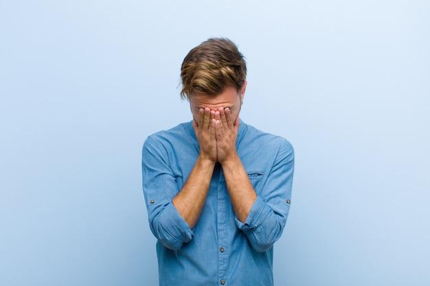 Jonge zakenman die droevig, gefrustreerd, zenuwachtig en depressief voelen, die gezicht behandelen met beide handen, huilend over blauwe muur