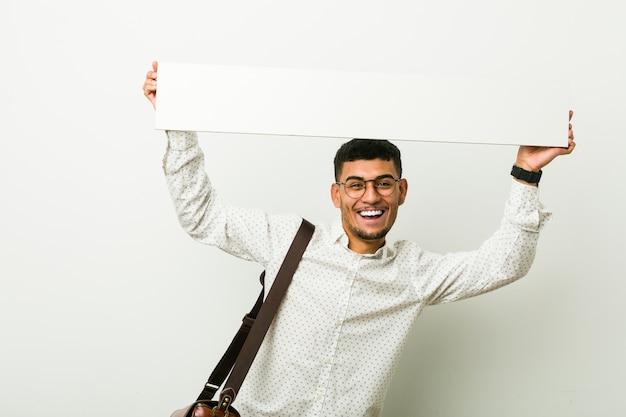 Jonge zakenman die een aanplakbiljet houdt