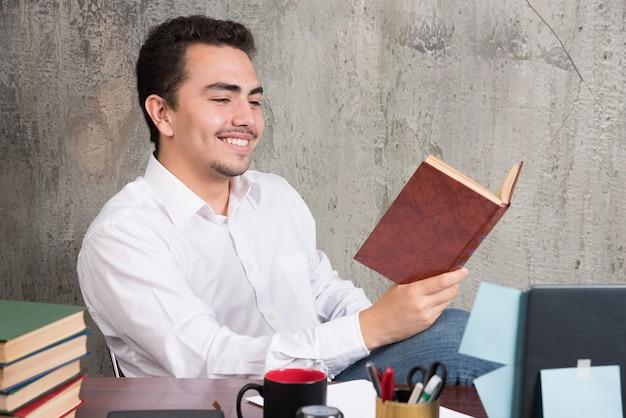 Jonge zakenman die een boek met gelukkige uitdrukking leest.