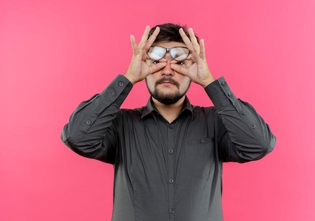 Jonge zakenman die een bril draagt die maskergebaar toont dat op roze muur wordt geïsoleerd