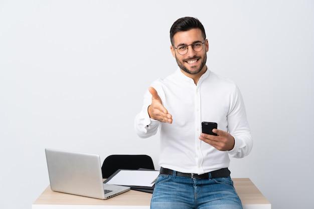 Jonge zakenman die een mobiel telefoonhandenschudden na goede deal houden