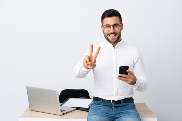 Jonge zakenman die een mobiele telefoon houdt die en overwinningsteken glimlacht toont