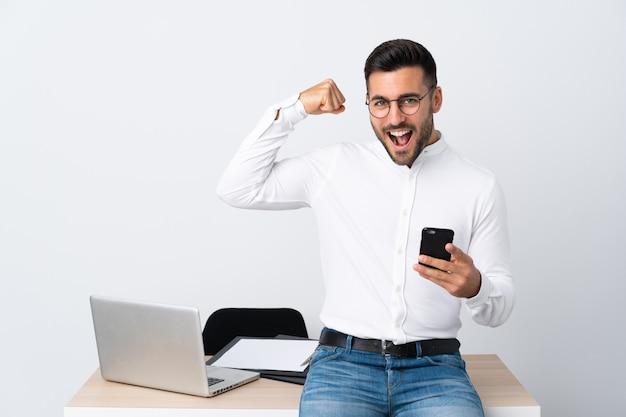 Jonge zakenman die een mobiele telefoon houdt die sterk gebaar maakt