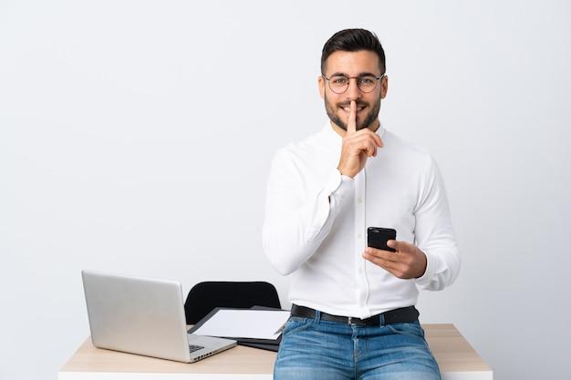 Jonge zakenman die een mobiele telefoon houdt die stiltegebaar doet