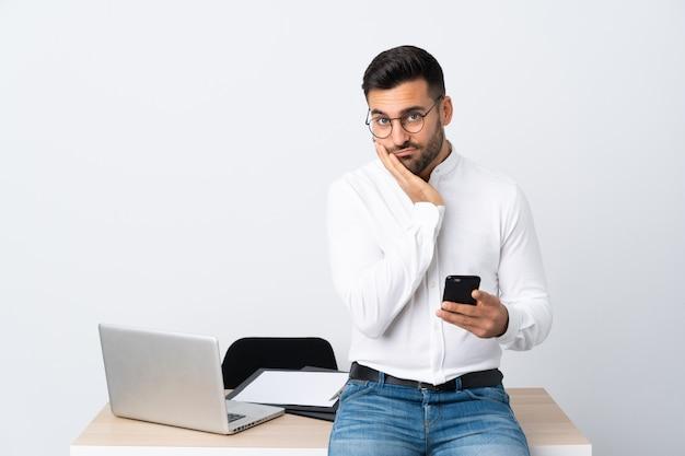 Jonge zakenman die een mobiele telefoon ongelukkig en gefrustreerd houdt
