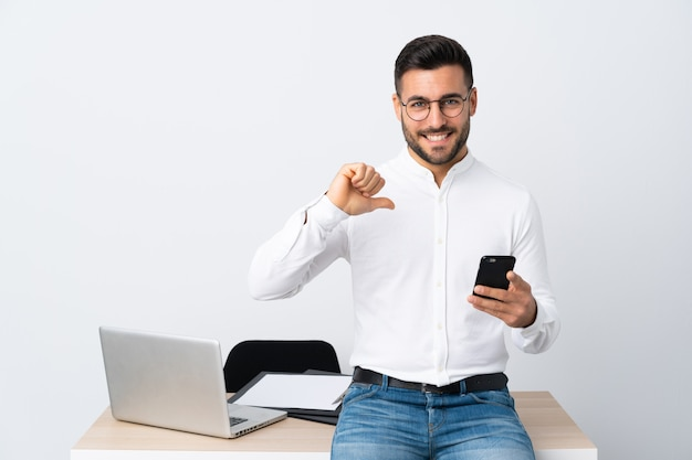 Jonge zakenman die een mobiele telefoon trots en zelfvoldaan houdt