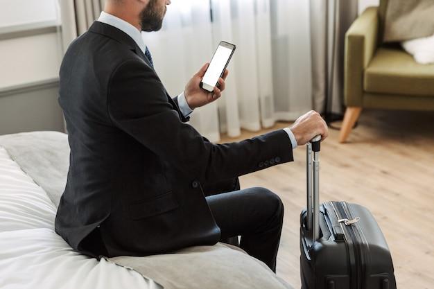 Jonge zakenman die een pak draagt dat in de hotelkamer zit en een mobiele telefoon met een leeg scherm gebruikt terwijl hij een koffer draagt
