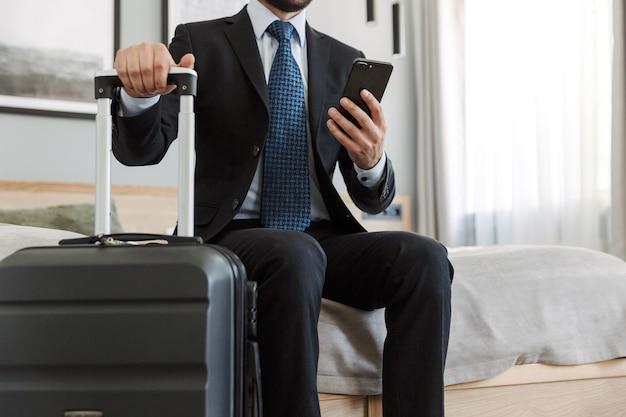 Jonge zakenman die een pak draagt dat in de hotelkamer zit, mobiele telefoon gebruikt terwijl hij een koffer draagt