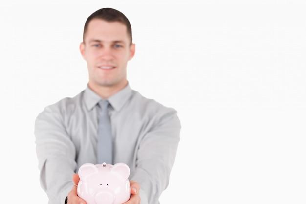 Jonge zakenman die een spaarvarken houdt