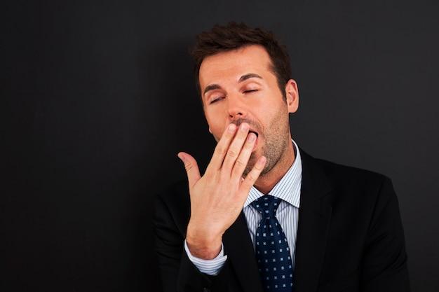 Jonge zakenman die en zijn mond geeuwt behandelt