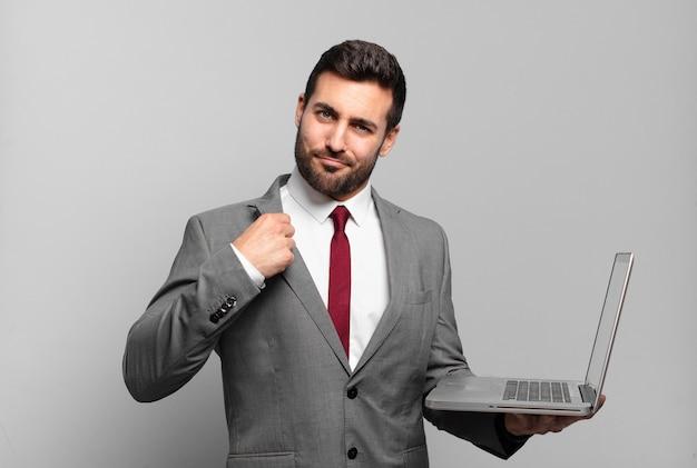 Jonge zakenman die er arrogant, succesvol, positief en trots uitziet, naar zichzelf wijst en een laptop vasthoudt