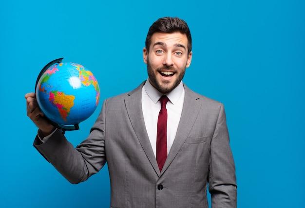 Jonge zakenman die er blij en aangenaam verrast uitziet, opgewonden met een gefascineerde en geschokte uitdrukking met een wereldbolkaart