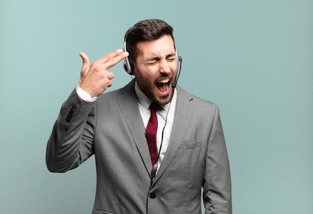 Jonge zakenman die er ongelukkig en gestrest uitziet, zelfmoordgebaar maakt een pistoolteken met de hand, wijzend naar het telemarketingconcept