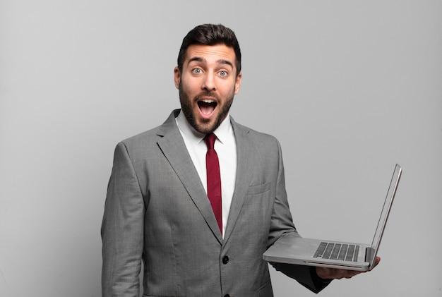 Jonge zakenman die erg geschokt of verrast kijkt, met open mond starend wauw zegt en een laptop vasthoudt