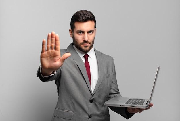 Jonge zakenman die ernstig, streng, ontevreden en boos kijkt die open palm toont die eindegebaar maakt en laptop houdt