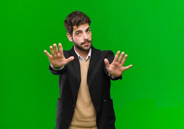 Jonge zakenman die ernstige, ongelukkige, boze en ontstemde ingang verbiedt of einde zegt met beide open palmen tegen groene achtergrond