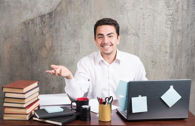 Jonge zakenman die gelukkig camera bij het bureau bekijkt.