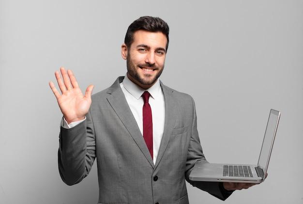 Jonge zakenman die gelukkig en opgewekt glimlacht, hand zwaait, u verwelkomt en begroet, of afscheid neemt en een laptop vasthoudt