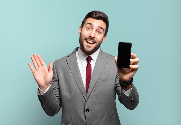 Jonge zakenman die gelukkig en opgewekt glimlacht, met de hand zwaait, je verwelkomt en begroet, of afscheid neemt en zijn telefoonscherm laat zien