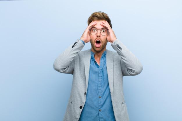 Jonge zakenman die geschokt en geschokt voelt, handen opheft en in paniek raakt bij een fout