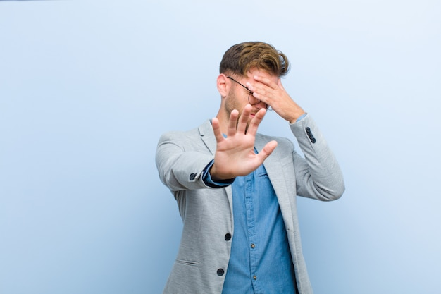 Jonge zakenman die gezicht behandelen met hand en andere hand vooraan zetten om camera tegen te houden, die foto's of beelden weigeren tegen blauw