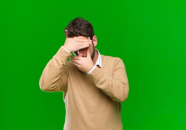 Jonge zakenman die gezicht behandelt met beide handen die nr zeggen tegen groene muur