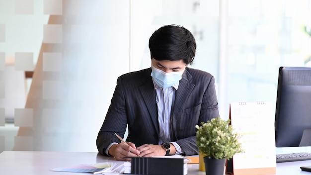 Jonge zakenman die gezichtsmasker draagt concentraat het schrijven van informatie over document terwijl het zitten in bureauruimte.