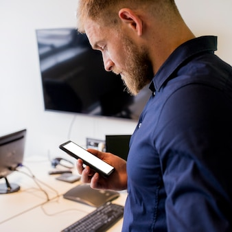 Jonge zakenman die het lege mobiele scherm bekijkt