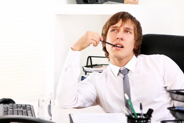 Jonge zakenman die in bureau denkt