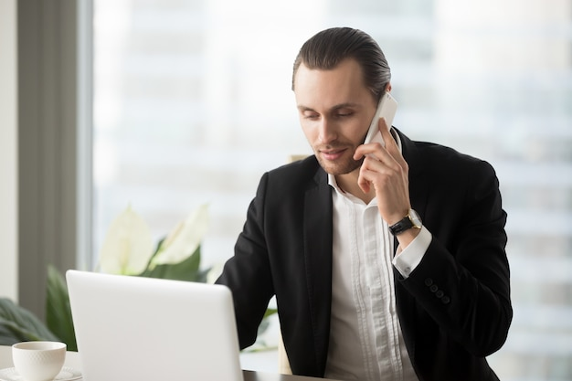 Jonge zakenman die in bureau laptop bekijkt