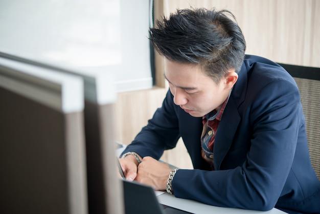 Jonge zakenman die in een bureau werkt