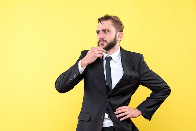 Jonge zakenman die in gedachten over geel wordt verloren