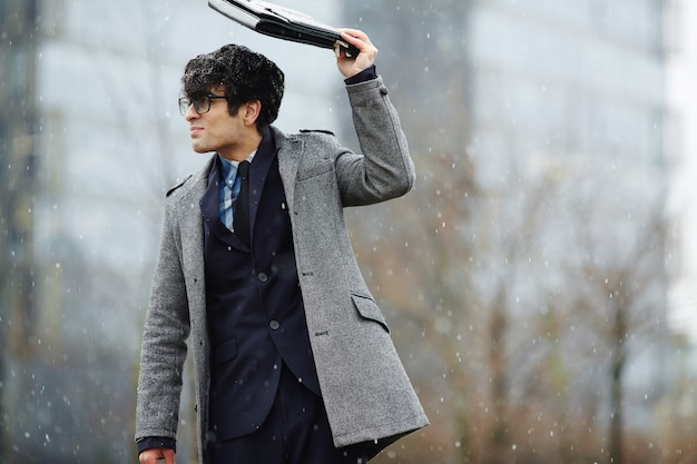 Jonge zakenman die in sneeuwval loopt
