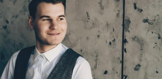 Jonge zakenman die in wit overhemd op een steenmuur glimlacht die weg eruit ziet