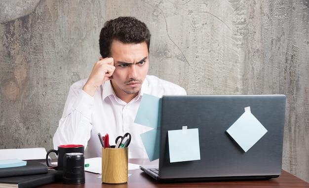 Jonge zakenman die laptop met gekke uitdrukking bekijkt bij het bureau.