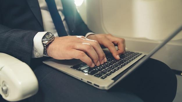Jonge zakenman die laptopcomputer in vliegtuig met behulp van