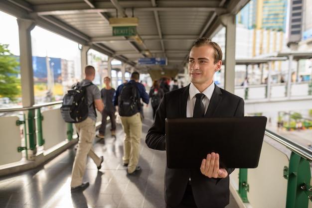 Jonge zakenman die laptopcomputer met behulp van in stad