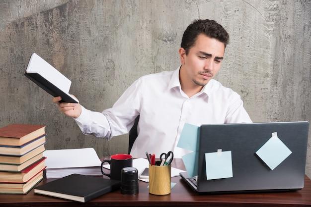 Jonge zakenman die met boek laptop bekijkt bij het bureau.