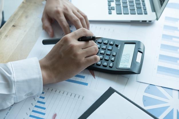 Jonge zakenman die met calculator, bedrijfsdocumenten en laptop werkt