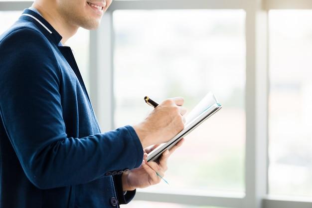 Jonge zakenman die met een notitieboekje werkt