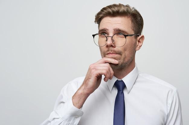 Jonge zakenman die met ernstige gezichtsuitdrukking over vraag denkt
