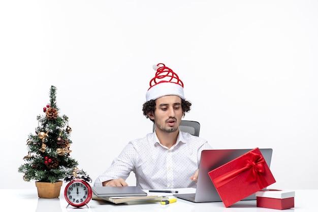 Jonge zakenman die met grappige kerstmanhoed kerstmis viert op kantoor