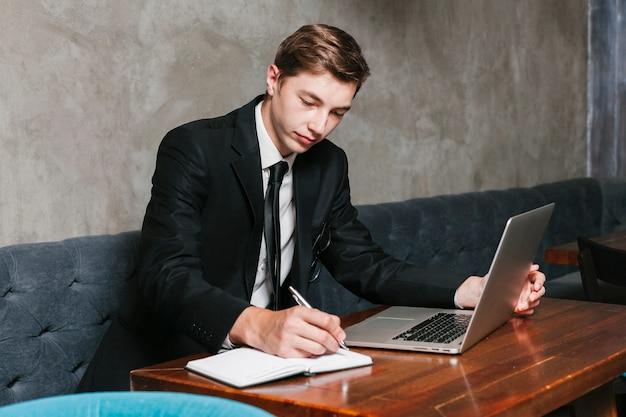 Jonge zakenman die met laptop werkt