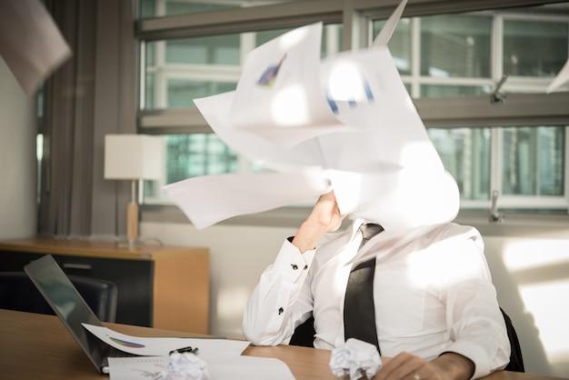 Jonge zakenman die met spanning in een bureau werkt
