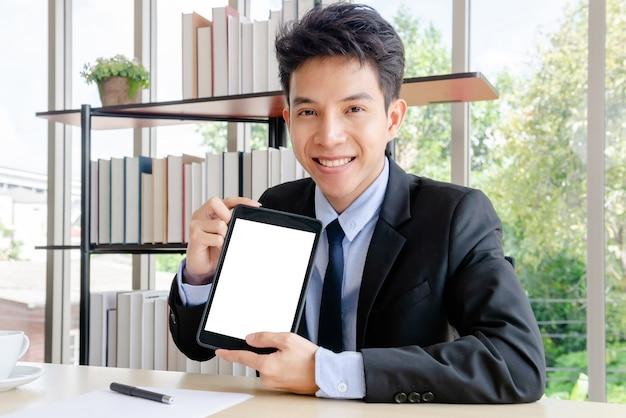 Jonge zakenman die met tablet werkt.
