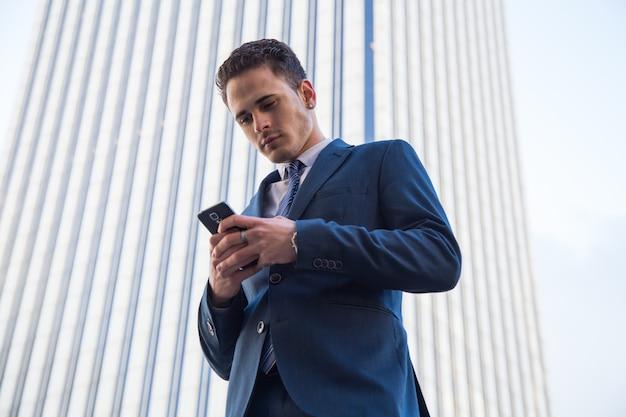 Jonge zakenman die met telefoon babbelt.
