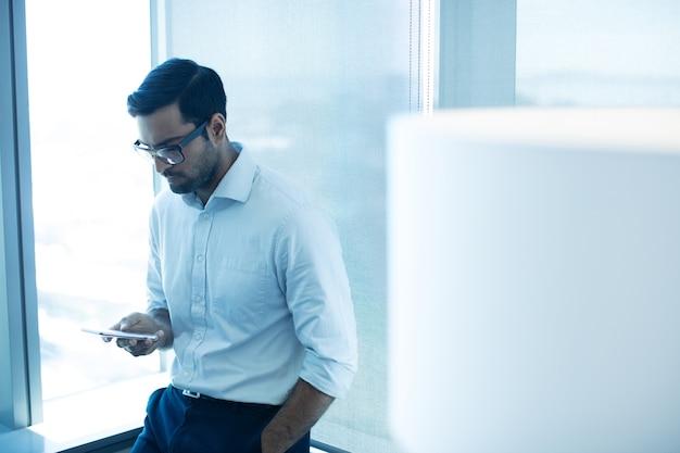Jonge zakenman die mobiele telefoon met behulp van terwijl leunend op glasvenster
