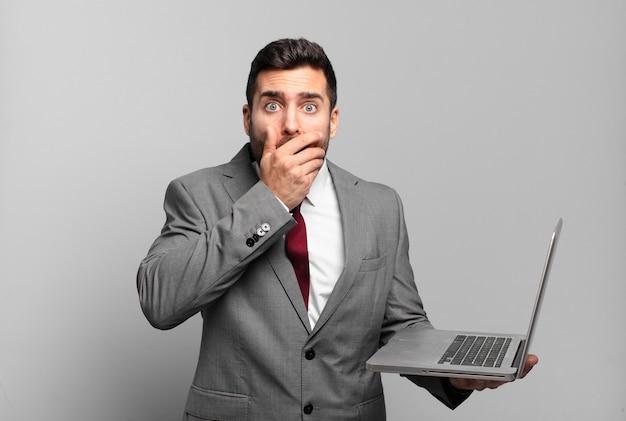 Jonge zakenman die mond bedekt met handen met een geschokte, verbaasde uitdrukking, een geheim houdt of oeps zegt en een laptop vasthoudt