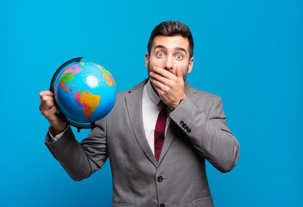 Jonge zakenman die mond bedekt met handen met een geschokte, verbaasde uitdrukking, een geheim houdt of oeps zegt met een wereldbolkaart