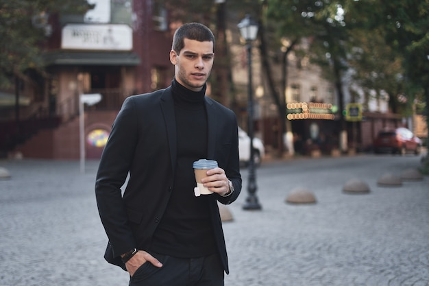 Jonge zakenman die naar het werk met koffie gaat
